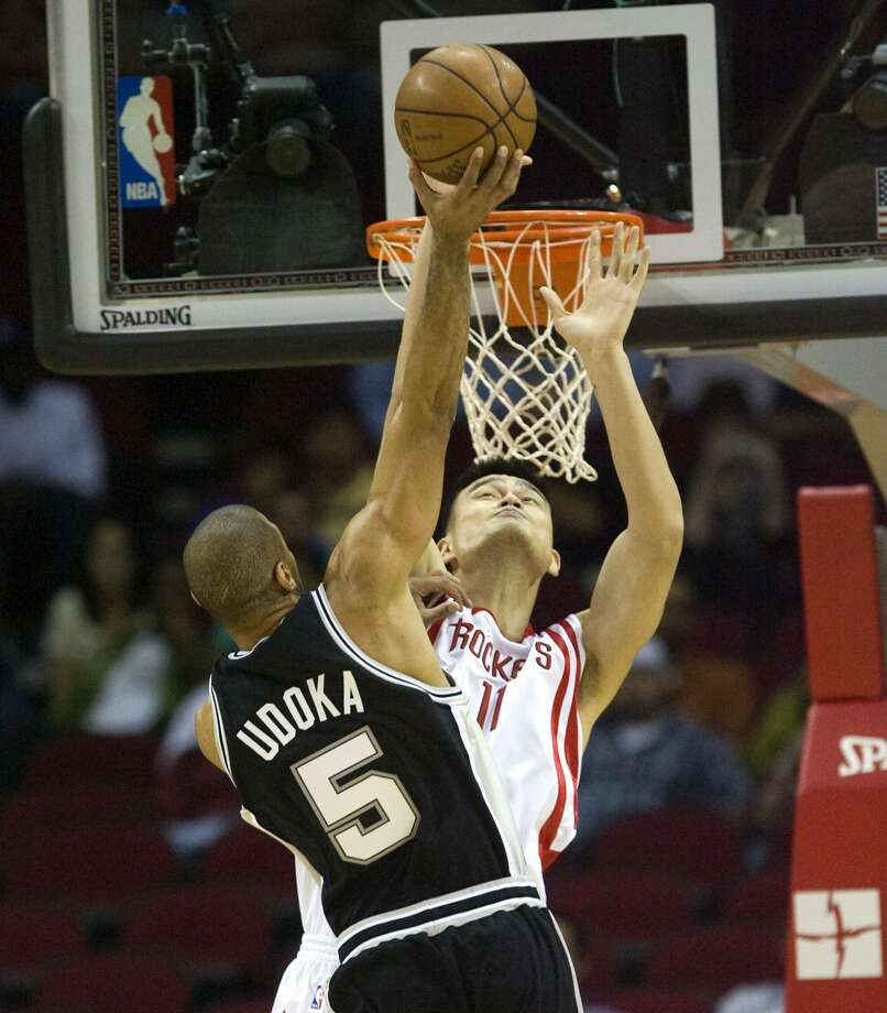 Spurs' Ime Udoka (5) drives to the basket over Houston Rockets' Yao Ming, of China, during the first half of a preseason NBA basketball game Thursday, Oct. 9, 2008, in Houston.  (Bob Levey / AP)