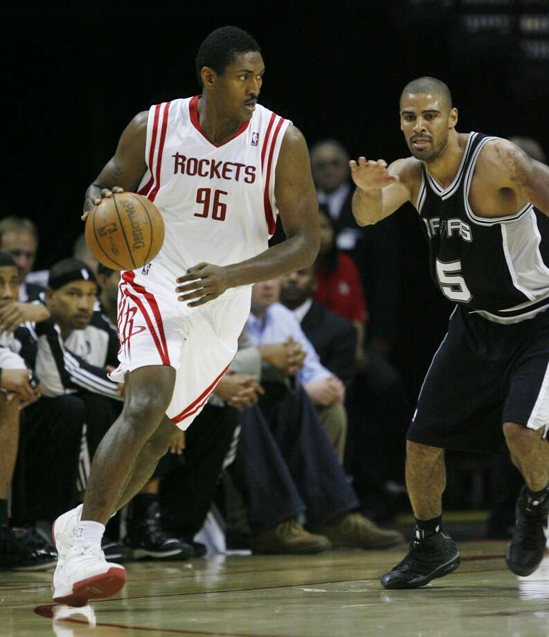 Houston Rockets' Ron Artest dribbles around San Antonio Spurs' Ime Udoka during the second half of a preseason NBA basketball game on Thursday, Oct. 9, 2008, in Houston. (Bob Levey / AP)