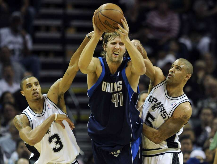 Dirk Nowitzki of the Dallas Mavericks looks to pass off as he is harassed by George Hill, left, and Ime Udoka of the Spurs during game five of the first round of NBA Western Conference playoffs on Tuesday, April 28, 2009. BILLY CALZADA / gcalzada@express-news.net (SAN ANTONIO EXPRESS-NEWS)