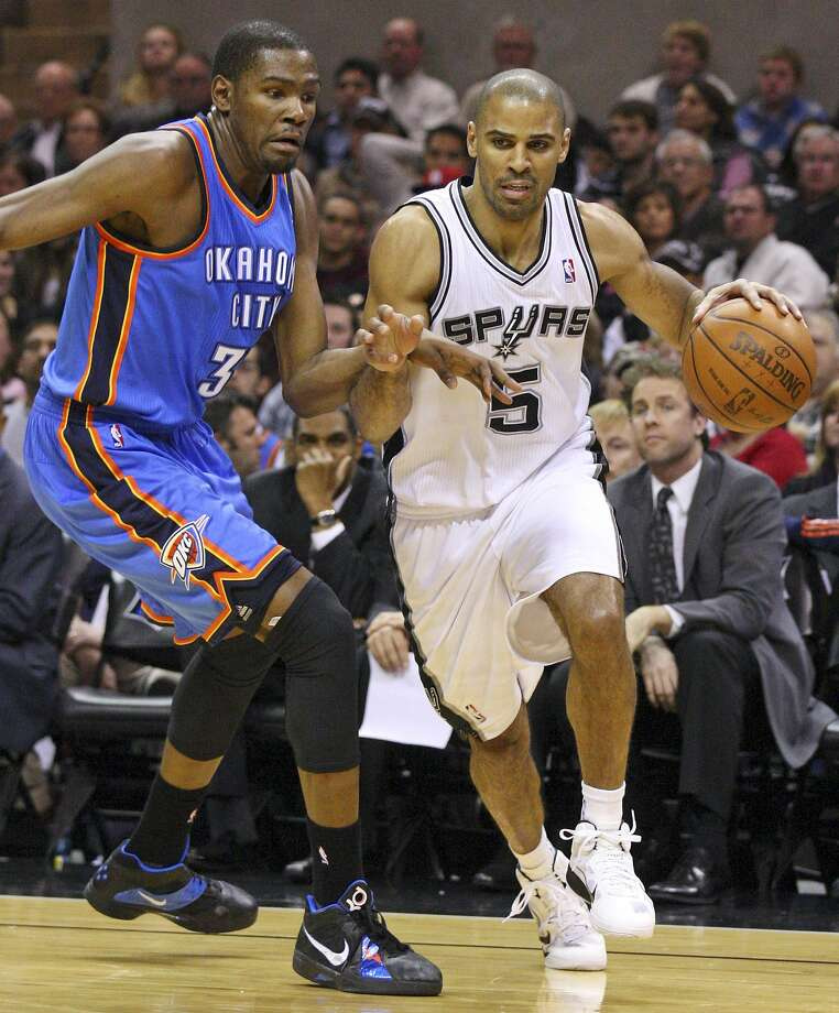 FOR SPORTS - Spurs' Ime Udoka looks for room around Thunder's Kevin Durant during second half action Saturday Jan. 1, 2011 at the AT&T Center. The Spurs won 101-74. (PHOTO BY EDWARD A. ORNELAS/eaornelas@express-news.net) (SAN ANTONIO EXPRESS-NEWS)