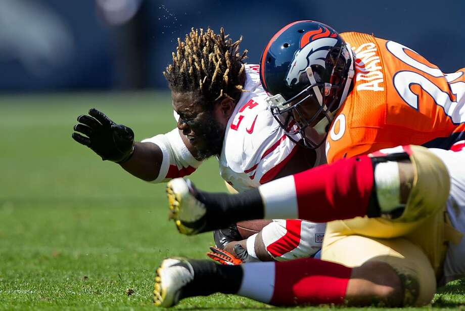 Anthony Dixon had a hair-raising experience as he was tackled by Broncos safety Mike Adams. Photo: Justin Edmonds, Getty Images