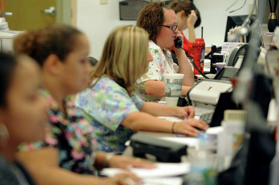 Kristy Blinn, right, works with other registrars in medical registration at Hometown Health in Schenectady, NY Friday Aug. 24, 2012. (Michael P. Farrell/Times Union) Photo: Michael P. Farrell