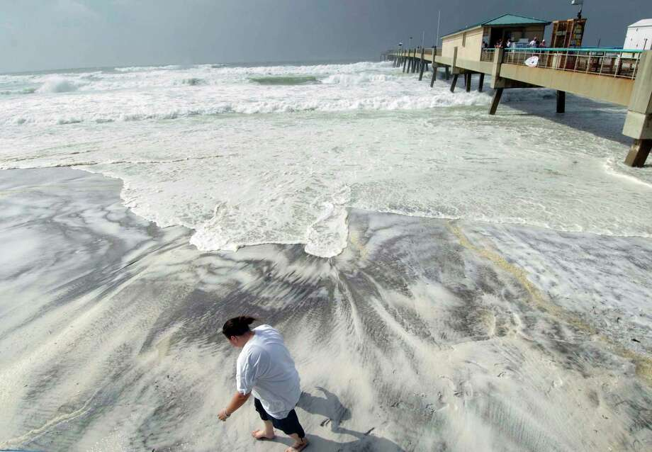L'Rena Anderson leans into the wind as she walks along the beach on Okaloosa Island in Fort Walton Beach, Fla., Tuesday, Aug. 28, 2012. Anderson was among many local residents who turned out to watch the effects of Hurricane Isaac as it churns through the Gulf of Mexico toward an expected landfall in Louisiana. (AP Photo/Northwest Florida Daily News, Devon Ravine) Photo: Devon Ravine
