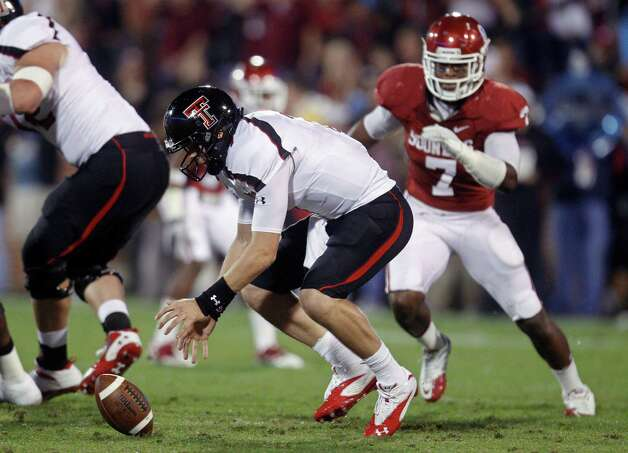 Texas Tech quarterback Seth Doege reaches to pick up a bad snap in front of Oklahoma linebacker Corey Nelson, right, in the first quarter of an NCAA college football game in Norman, Okla., Saturday, Oct. 22, 2011. (AP Photo/Sue Ogrocki) Photo: Sue Ogrocki, Associated Press / AP