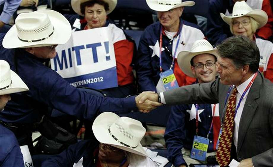 Texas Governor Rick Perry shakes hands with delegates during the Republican National Convention in Tampa, Fla., on Tuesday, Aug. 28, 2012. (AP Photo/Charlie Neibergall) (AP)