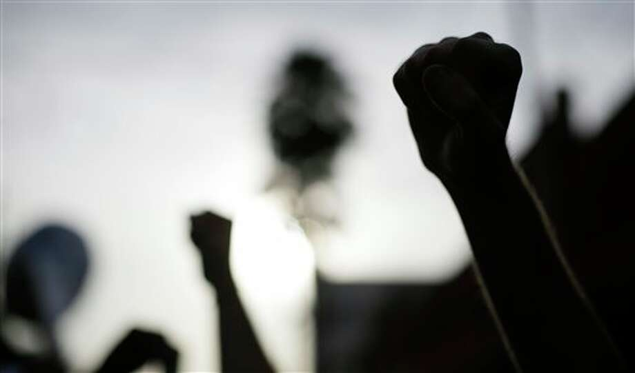 Demonstrators walk and raise their fists during a protest, Tuesday, Aug. 28, 2012, in the Ybor City section of Tampa, Fla. Protestors gathered in Tampa to march in demonstration against the Republican National Convention.(AP Photo/Patrick Semansky)