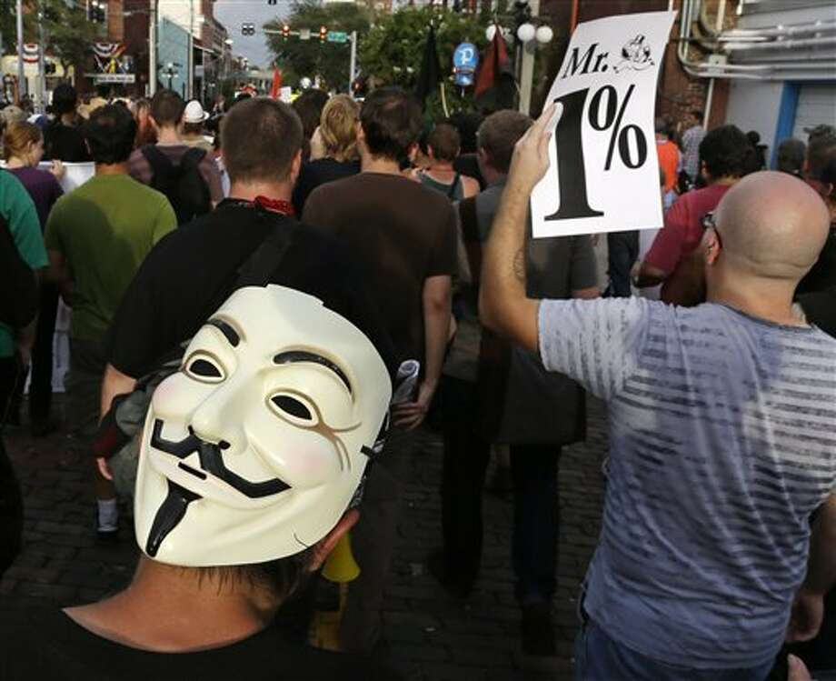 Demonstrators walk during a protest, Tuesday, Aug. 28, 2012, in the Ybor City section of Tampa, Fla. Protestors gathered in Tampa to march in demonstration against the Republican National Convention. (AP Photo/Chris O'Meara) (AP)