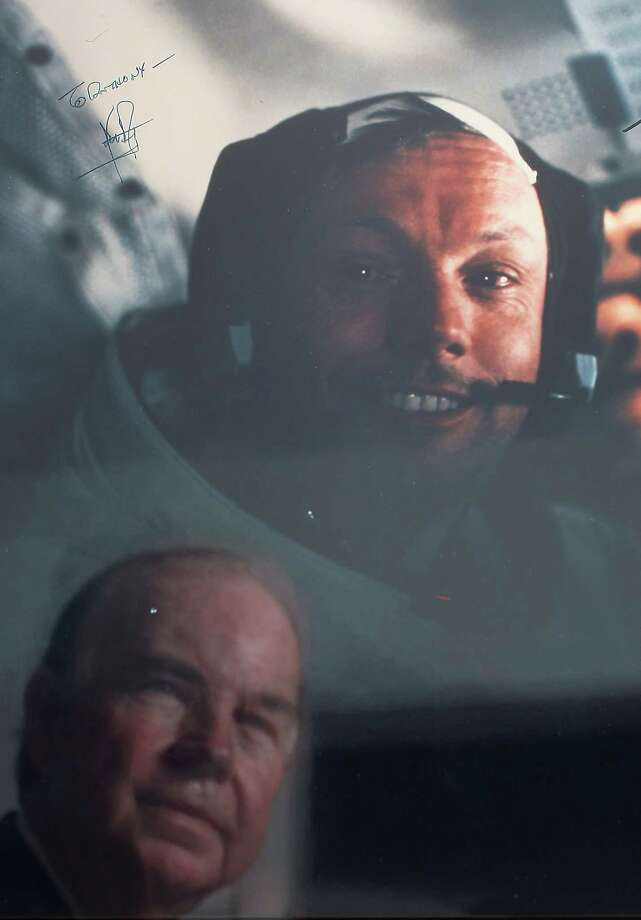 Anthony Pizzitola of Houston, who has edited a book on Neil Armstrong autographs, is reflected in a photograph of the astronaut, signed in 1989. Photo: Karen Warren / © 2012  Houston Chronicle