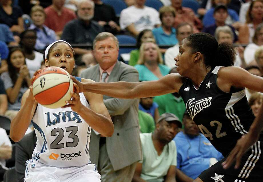 Minnesota Lynx forward Maya Moore (23) holds onto the ball as San Antontio Silver Stars guard Shenise Johnson (42) tries to push it out of her grip in the first half of a WNBA basketball game, Tuesday, Aug. 28, 2012, in Minneapolis. AP Photo/Stacy Bengs) Photo: Stacy Bengs, Associated Press / FR170489 AP