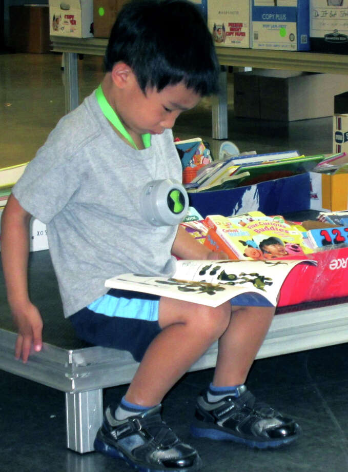 Avid young reader  Miguel Garcia, 7, of New Milford is a contented boy as he digs into books offered as part of last weekend's Friends of the Library book sale at New Milford High School. Large crowds flocked to NMHS for the four-day event featuring thousands of books from New Milford Public Library. For more photos, see next week's Greater New Milford Spectrum and check www.newmilfordspectrum.com. Photo: Norm Cummings