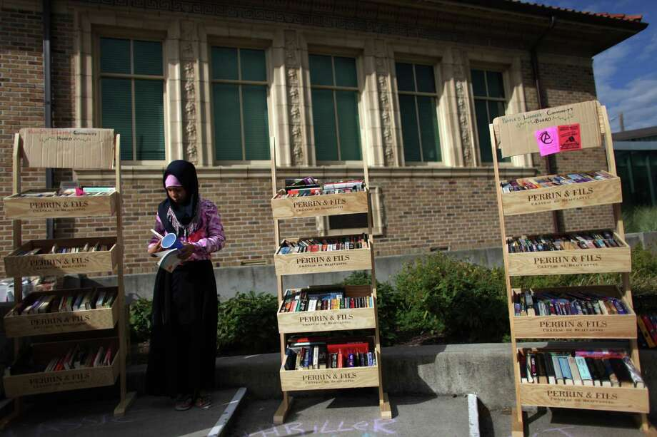 Khabirah Weedington, 11, browses books at 'The People's Library' set up in front of the Douglass-Truth branch of the Seattle Public Library in the Central District during a week-long closure of the library, part of measures to trim from the budget. She was hunting for a particular book popular among 'tweens.' Photo: JOSHUA TRUIJLLO / SEATTLEPI.COM
