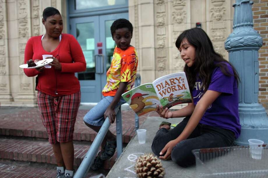 Andrea Hernandez-Mills reads a book on the steps of the Douglass-Truth Branch of the Seattle Public Library during a week-long closure of the facility, part of measures to trim from the city budget. Photo: JOSHUA TRUIJLLO / SEATTLEPI.COM