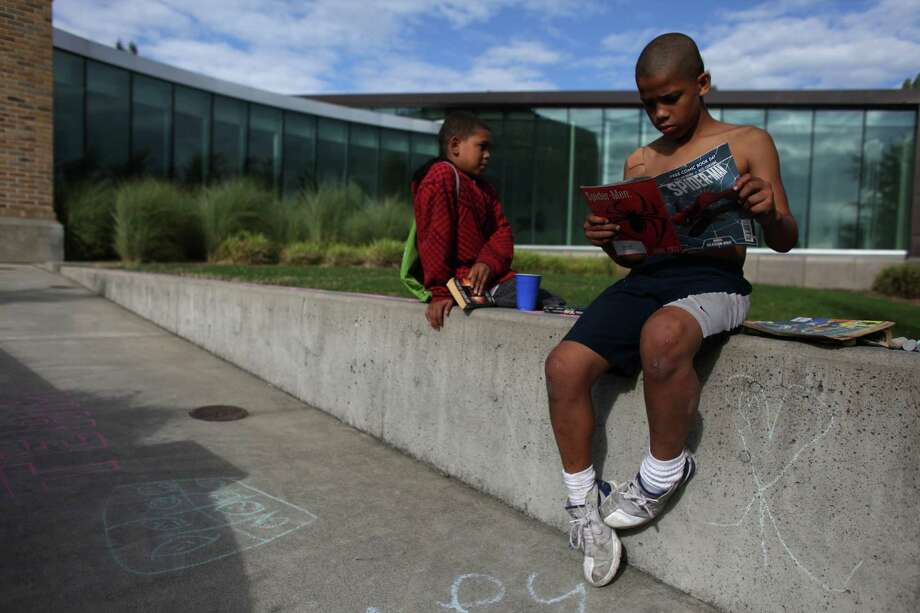 Ishmael Weddington, 10, reads a comic book from 'The People's Library'  in front of the Douglass-Truth Branch of the Seattle Public Library during a week-long closure of the facility. Photo: JOSHUA TRUIJLLO / SEATTLEPI.COM