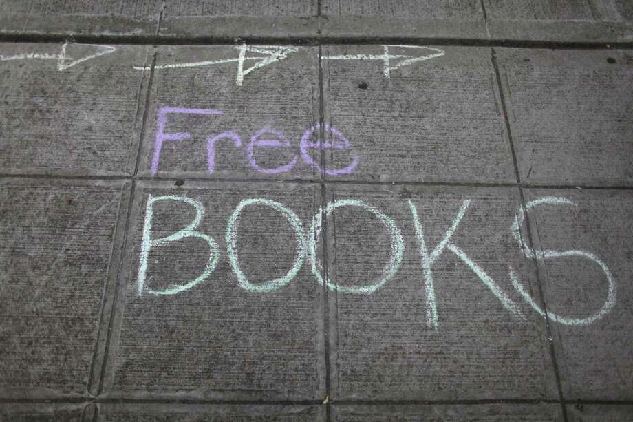 Chalk directs people to 'The People's Library' set up in front of the Douglass-Truth branch of the Seattle Public Library during a week-long closure of the library system, part of measures to trim from the city budget. 'The People's Library' was organized in response to the closure by community members and some members of the Occupy movement. The temporary library was a hit with neighborhood residents, drawing small crowds to browse the donated books, games and toys. Photo: JOSHUA TRUIJLLO / SEATTLEPI.COM