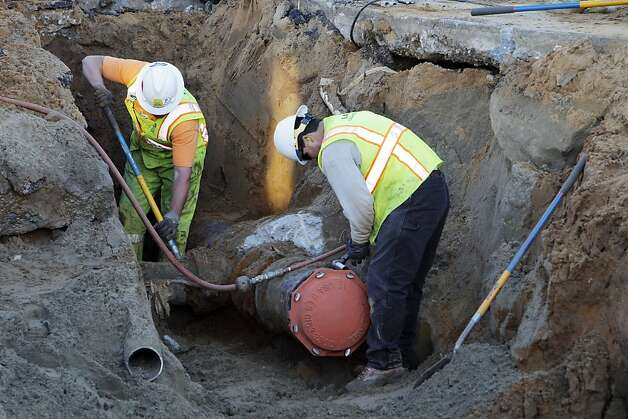 Crews work to cap a 12-inch line that was broken from the damage to the road after a water main ruptured at the intersection of Sunnydale Avenue and Cora Street in San Francisco, Calif., on Tuesday, August 28, 2012. Photo: Carlos Avila Gonzalez, The Chronicle