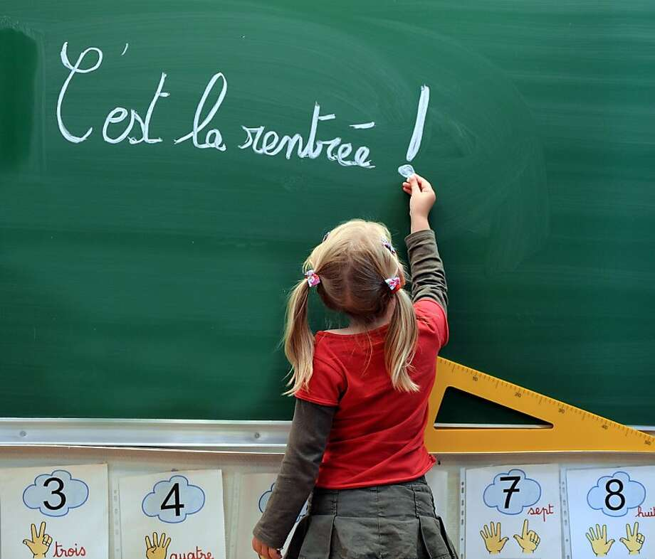 """A little  girl writes on the blacboard """"C'est la rentrée"""" (Its the Start of the school year) at the school Jules Ferry in Bethune, northern, France, on August 28, 2012, a few days of the start of classes. Photo: Denis Charlet, AFP/Getty Images"""