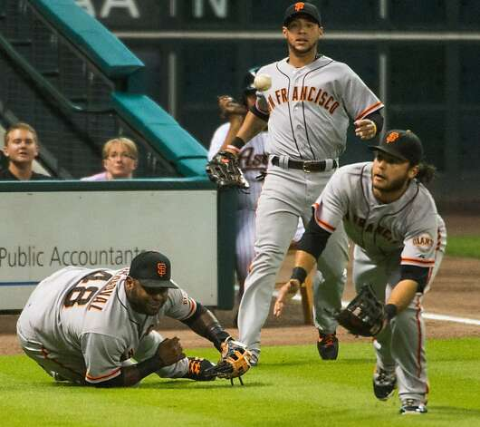 Giants third baseman Pablo Sandoval, left, watches as shortstop Brandon Crawford raced toward a misplayed a foul ball off the bat of Astros catcher Jason Castro  during the first inning at Minute Maid Park on Tuesday, Aug. 28, 2012, in Houston. Sandoval knocked the ball high in the air and Giants shortstop Brandon Crawford raced in to scoop the ball off the turf for the third out. ( Smiley N. Pool / Houston Chronicle ) Photo: Smiley N. Pool, Houston Chronicle