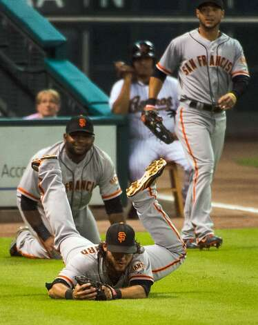 Giants shortstop Brandon Crawford dives to catch a misplayed a foul ball off the bat of Astros catcher Jason Castro during the first inning at Minute Maid Park on Tuesday, Aug. 28, 2012, in Houston. Giants third baseman Pablo Sandoval, background, knocked the ball high in the air and Giants shortstop Brandon Crawford raced in to scoop the ball off the turf for the third out. ( Smiley N. Pool / Houston Chronicle ) Photo: Smiley N. Pool, Houston Chronicle