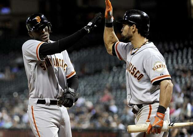 San Francisco Giants' Joaquin Arias, left, is congratulated by Angel Pagan after scoring the go-ahead run to defeat the Houston Astros 3-2 in a baseball game, Tuesday, Aug. 28, 2012, in Houston. (AP Photo/Pat Sullivan) Photo: Pat Sullivan, Associated Press