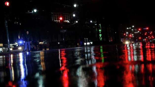 Lights are reflected on Canal Street as a police officer patrolling the area passes a pedestrian as storm bands from Hurricane Isaac hit, Tuesday, Aug. 28, 2012, in New Orleans, Louisiana. Isaac, a massive storm spanning nearly 200 miles from its center, made landfall  Tuesday evening near the mouth of the Mississippi River. Photo: Eric Gay