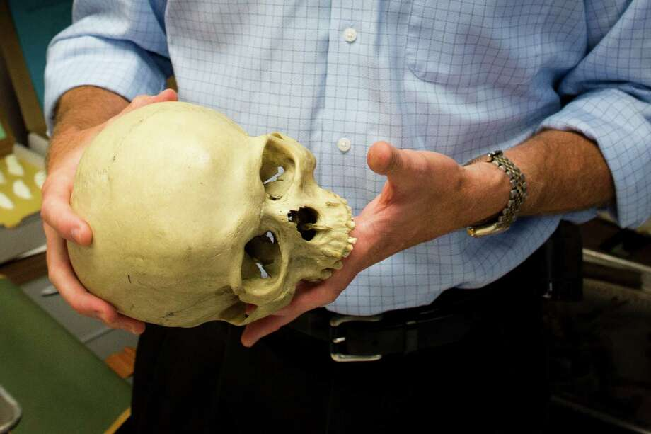 Bradley Adams, Ph.D., Director of Forensic Anthropology at the City of New York Office of Chief Medical Examiner handles anatomical specimens in a laboratory, Tuesday, Aug. 14, 2012, in New York. The office is undertaking an ambitious effort to identify the nameless dead in the city's potter's field, seeking to capitalize on the expertise that it gained over the last decade identifying remains from the World Trade Center attack. Photo: John Minchillo, AP / FR170537 AP