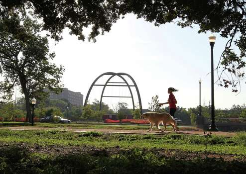 A woman jogs with a dog along a hike and bike trial around Hermann Park Golf Course Wednesday, Aug. 29, 2012, in Houston. Photo: James Nielsen / © Houston Chronicle 2012
