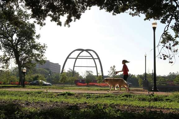 A woman jogs with a dog along a hike and bike trial around Hermann Park Golf Course Wednesday, Aug. 29, 2012, in Houston.