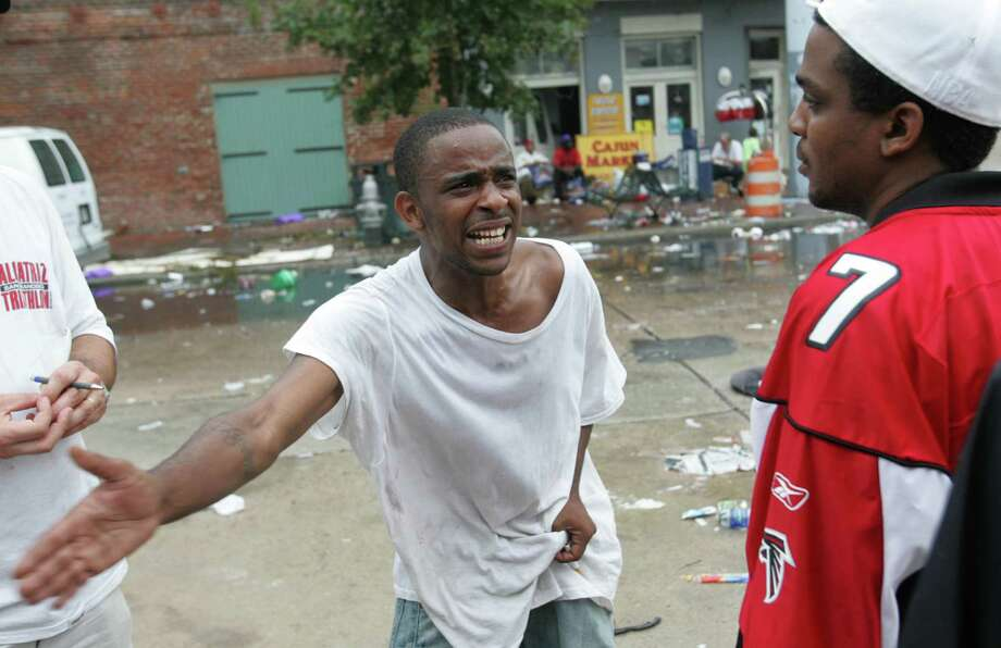 A Hurricane Katrina victim yells to another victim about the dreadful conditions outside the convention center Thursday, Sept. 1, 2005, in New Orleans. La. Photo: BRETT COOMER, HOUSTON CHRONICLE / HOUSTON CHRONICLE