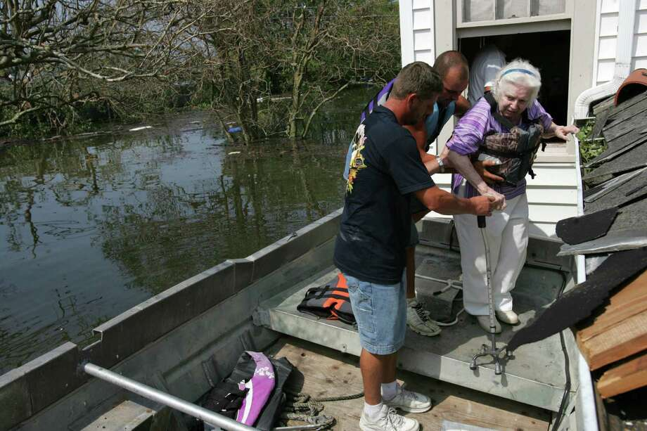 Ernest Gary, left, and Richard Boutte help Marion Lee onto a boat as she is rescued the second story window of her flooded home caused by Hurricane Katrina Tuesday, Aug. 30, 2005, in New Orleans, La. Photo: BRETT COOMER, HOUSTON CHRONICLE / HOUSTON CHRONICLE