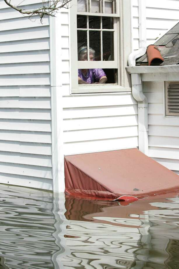 Marion Lee looks out the second story window waiting to be rescued from her flooded out home caused by Hurricane Katrina Tuesday, Aug. 30, 2005, in New Orleans, La. Photo: BRETT COOMER, HOUSTON CHRONICLE / HOUSTON CHRONICLE
