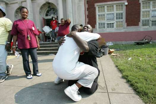Hiram Chapman embraces Darren Watson after Watson dropped to his knees to pray Saturday, Sept. 3, 2005, outside Colton Middle School, where Chapman and Watson have been leading a community of Hurricane Katrina survivors since the storm in New Orleans, La. Photo: BRETT COOMER, HOUSTON CHRONICLE / HOUSTON CHRONICLE