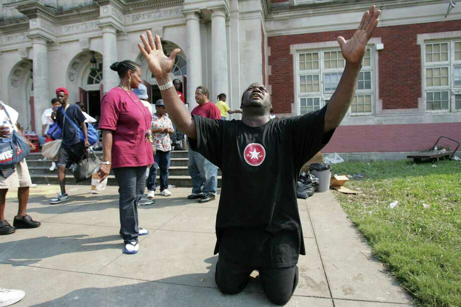 Darren Watson drops to his knees to pray outside Colton Middle School where Watson has been leading a group of Hurricane Katrina survivors living in the school Saturday, Sept. 3, 2005, in New Orleans, La. Photo: BRETT COOMER, HOUSTON CHRONICLE / HOUSTON CHRONICLE