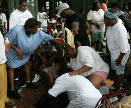 Hurricane Katrina victims waiting outside the convention center try to help a woman suffering from a seizure Thursday, Sept. 1, 2005, in New Orleans. La. Photo: BRETT COOMER, HOUSTON CHRONICLE / HOUSTON CHRONICLE