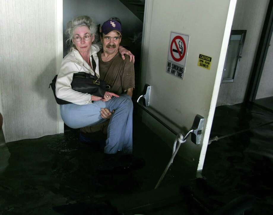 A Hurricane Katrina victim is carried out of an office building where she was one of 75 storm victims spent nearly two days after floodwaters from the storm invaded their homes Tuesday, Aug. 30, 2005, in New Orleans, La. Photo: BRETT COOMER, HOUSTON CHRONICLE / HOUSTON CHRONICLE