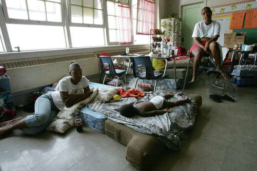 A pair of women sit in a classroom at Colton Middle School Saturday, Sept. 3, 2005, in New Orleans, La., where a group of about 225 Hurricane Katrina survivors have been living as a community since the storm ravaged the city. Photo: BRETT COOMER, HOUSTON CHRONICLE / HOUSTON CHRONICLE