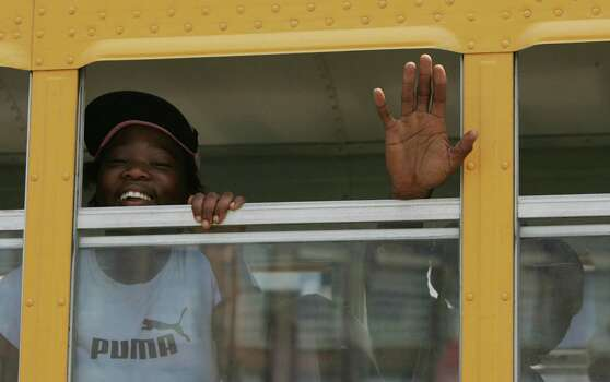 A pair of Hurricane Katrina survivors smile and wave out the window of a school bus as they evacuate from the convention center Saturday, Sept. 3, 2005, in New Orleans, La. Photo: BRETT COOMER, HOUSTON CHRONICLE / HOUSTON CHRONICLE