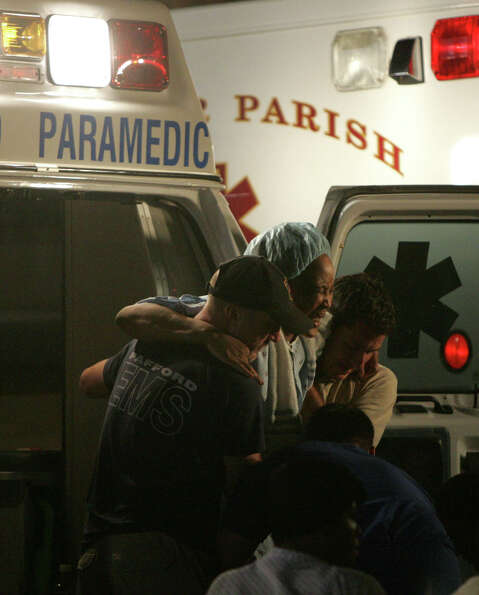 Sick and injured victims of Hurricane Katrina are unloaded from ambulances to be cared for at a make