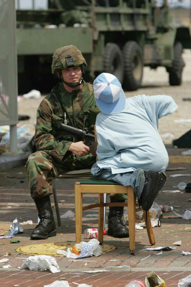 Spc. Michael Mathews, of the Arkansas National Guard, talks with Jermaine Williams, 11, as relief efforts begin for the victims of Hurricane Katrina Friday, Sept. 2, 2005, in New Orleans. La. Photo: BRETT COOMER, HOUSTON CHRONICLE / HOUSTON CHRONICLE