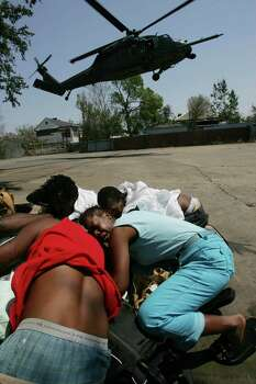 Stella Nelson, 41, (in blue) huddles with a group of Hurricane Katrina victims as an evacuation helicopter lands in their 8th Ward neighborhood to get them out Sunday, Sept. 4, 2005, in New Orleans, La. Photo: BRETT COOMER, HOUSTON CHRONICLE / HOUSTON CHRONICLE