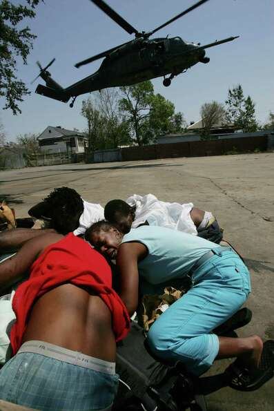 Stella Nelson, 41, (in blue) huddles with a group of Hurricane Katrina victims as an evacuation heli