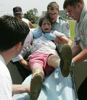 A woman screams as she is put on a stretcher after being airlifted from her flooded out home caused by Hurricane Katrina Tuesday, Aug. 30, 2005, in New Orleans, La. Photo: BRETT COOMER, HOUSTON CHRONICLE / HOUSTON CHRONICLE