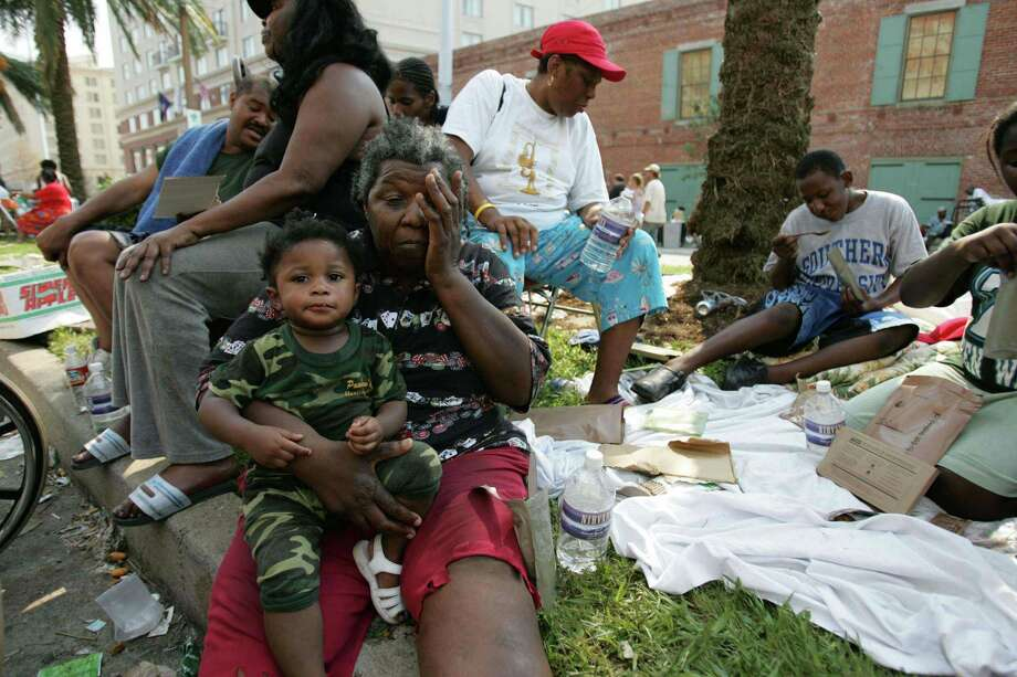 Mary Woods holds Joshanna Miner as they sit on the median outside the convention center after the National Guard brought food and water to the Hurricane Katrina victims Friday, Sept. 2, 2005, in New Orleans. La. Photo: BRETT COOMER, HOUSTON CHRONICLE / HOUSTON CHRONICLE