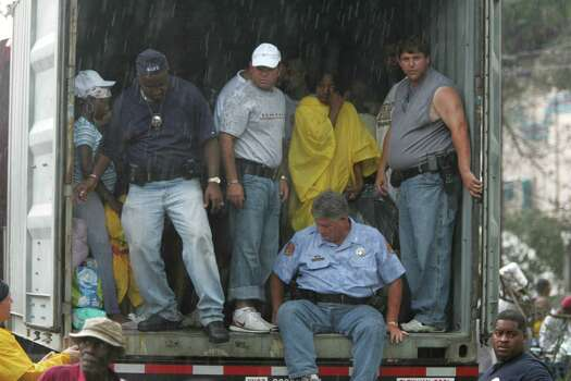 Rain begins to fall as New Orleans police officers guard the back of a truck that they just loaded with Hurricane Katrina victims Thursday, Sept. 1, 2005, in New Orleans. La. Photo: BRETT COOMER, HOUSTON CHRONICLE / HOUSTON CHRONICLE