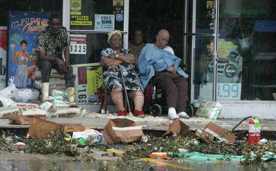 Hurricane Katrina victims sit outside a convenience store where they were stranded Thursday, Sept. 1, 2005, in New Orleans. La. Photo: BRETT COOMER, HOUSTON CHRONICLE / HOUSTON CHRONICLE