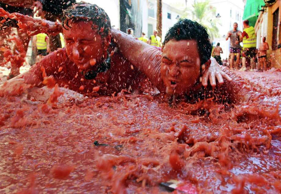 "Revelers  play in tomato pulp during the annual ""tomatina"" tomato fight fiesta in the village of Bunol, near Valencia, Spain, on Wednesday, Aug. 29, 2012. Bunol's town hall estimated more than 40,000 people, some from as far away as Japan and Australia, took up arms Wednesday with at least 100 tons of tomatoes in the yearly food fight known as the 'Tomatina' now in its 64th year. (AP Photo/Alberto Saiz) Photo: Ap/getty"