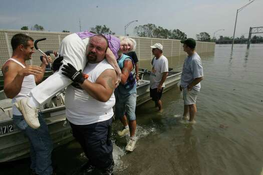 Jose Lopez carries Marion Lee from a rescue boat after she was  rescued from her flooded out home caused by Hurricane Katrina Tuesday, Aug. 30, 2005, in New Orleans, La. Photo: BRETT COOMER, HOUSTON CHRONICLE / HOUSTON CHRONICLE