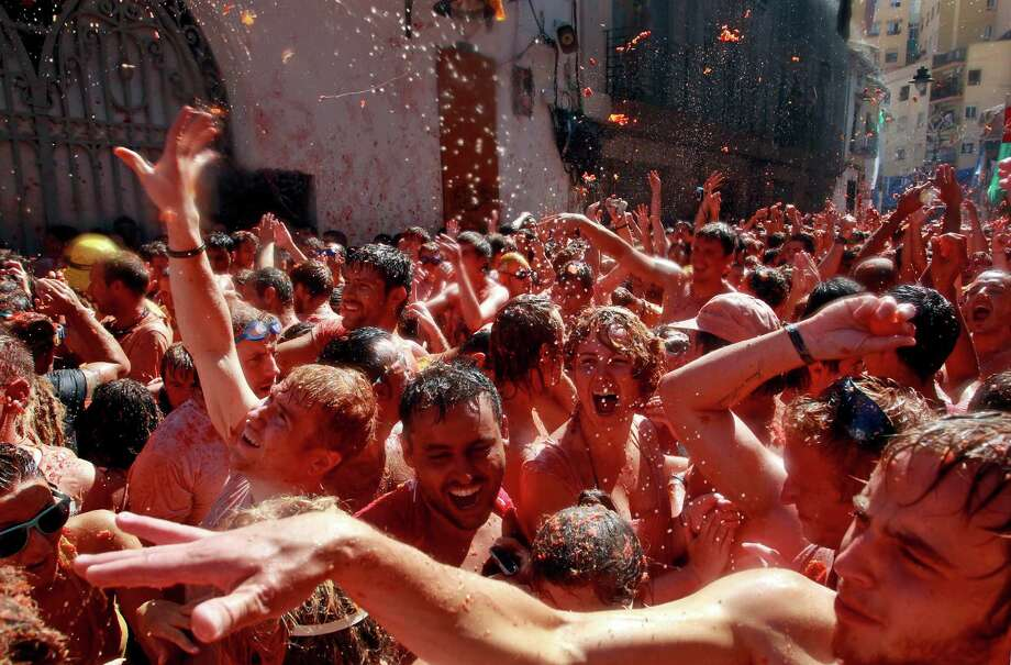 "Revelers throw tomatoes during the annual ""tomatina"" tomato fight fiesta in the village of Bunol, near Valencia, Spain, Wednesday, Aug. 29, 2012. Bunol's town hall estimated more than 40,000 people, some from as far away as Japan and Australia, took up arms Wednesday with 100 tons of tomatoes in the yearly food fight known as the 'Tomatina' now in its 64th year. (AP Photo/Alberto Saiz) Photo: Ap/getty"