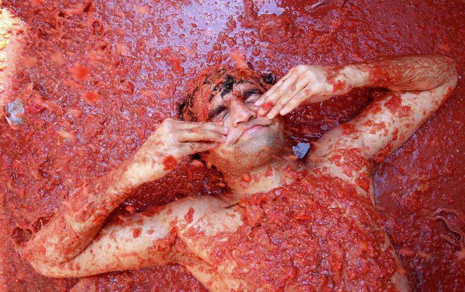 "A reveler wipes  tomato pulp from his face  during the annual ""tomatina"" tomato fight fiesta in the village of Bunol, near Valencia, Spain, Wednesday. Bunol's town hall estimated more than 40,000 people, some from as far away as Japan and Australia, took up arms Wednesday with at least 100 tons of tomatoes in the yearly food fight known as the 'Tomatina' now in its 64th year. (AP Photo/Alberto Saiz) Photo: Ap/getty"