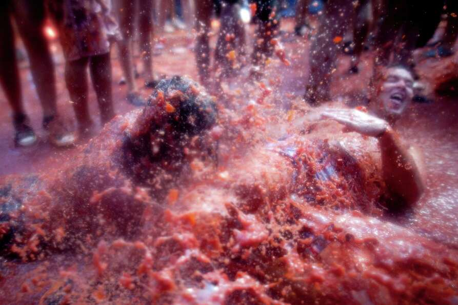 Revelers are covered in tomato pulp while participating the annual Tomatina festival on Wednesday in