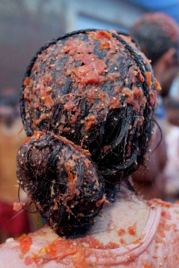 A reveler's hair is covered in tomato pulp while participating the annual Tomatina festival on Wednesday in Bunol, Spain. Thousands of people threw 120 tons of ripe tomatoes in the world's biggest tomato fight held annually in this Spanish Mediterranean town.  (Photo by Pablo Blazquez Dominguez/Getty Images) Photo: Pablo Blazquez Dominguez, Ap/getty / 2012 Getty Images